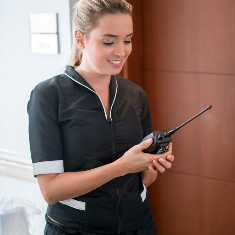 Housekeeper wearing a uniform and working at a hotel using a radio to communicate
