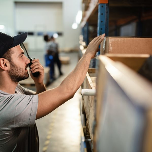 Young male worker checking packages on a shelf while using walkie-talkie in distribution warehouse.