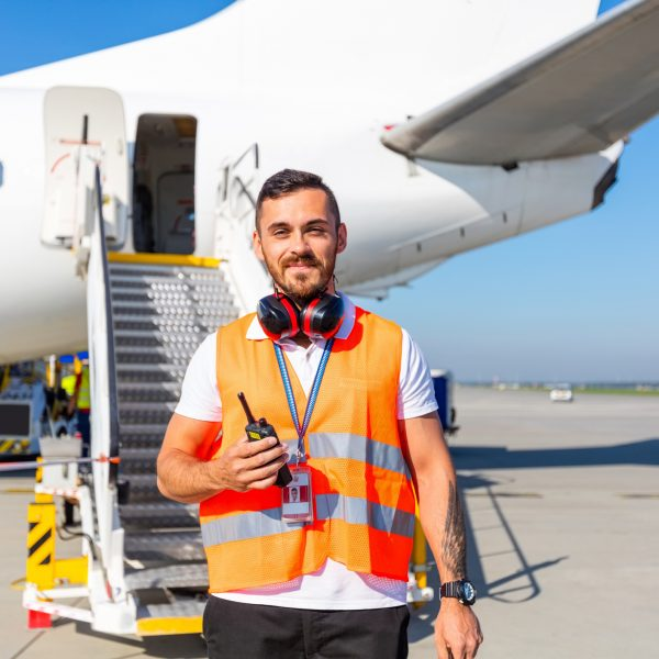 Outdoor shot of young man standing outside in front of airplane with headphone and walkie-talkie. Airport ground crew at work.